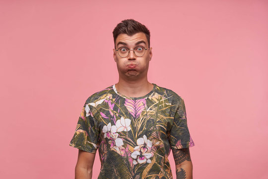 Indoor shot of cute guy in flowered t-shirt with wide eyes open standing over pink background, trying to hold breath, making funny grimace