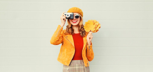 happy smiling woman with autumn yellow maple leaves, retro camera taking picture in french beret over gray wall background