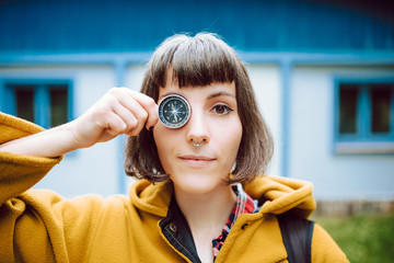 Cheerful young woman crossing eyes and holding retro compass near face while standing on blurred background of countryside house
