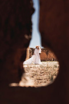 Through hole view of elegant woman in white dress inside walls of ancient fortress on daytime