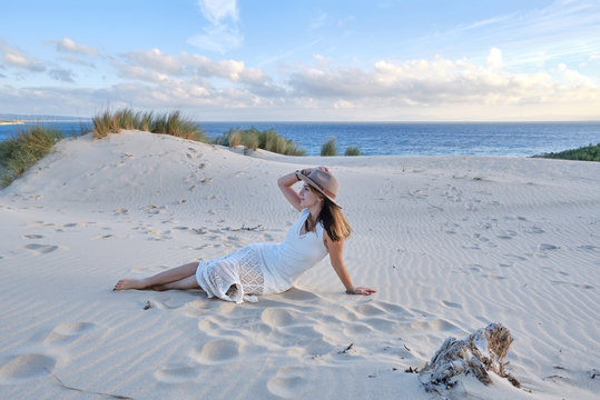 Young beautiful woman in white dress and hat lying on sandy beach in Tarifa, Spain