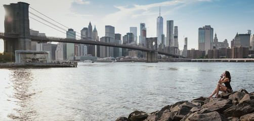 woman sitting on rocks in brooklyn looking the bridge and manhattan in a sunny day