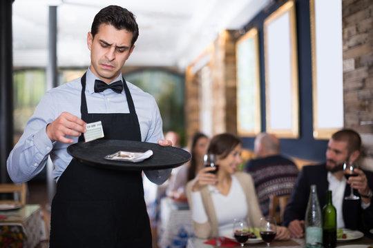 male waiter keeps money for the order