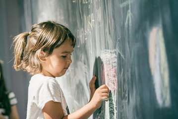 Beautiful little girl drawing on a blackboard at playground