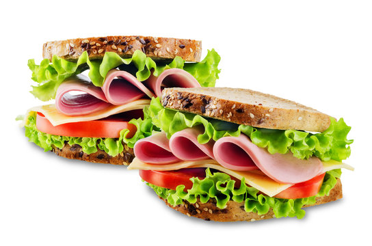 Sandwich with whole grain bread, salad, cheese, tomato and ham on a white isolated background