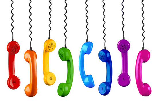 row of colorful rainbow colored old fashioned retro phone reciever with black telephone wire isolated white background, business communication support service concept