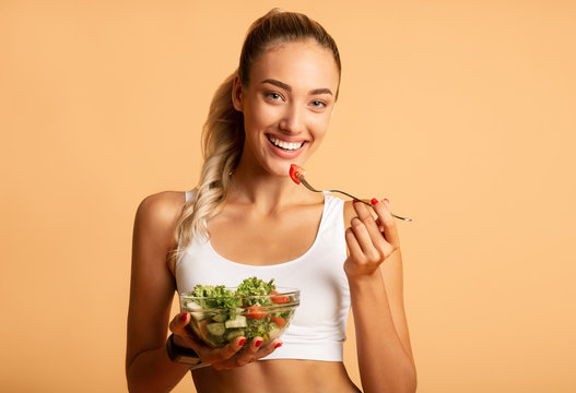 Fit Woman Eating Fresh Salad Over Pink Studio Background
