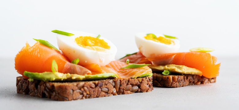 Healthy open sandwiches on multigrain wholegrain  toast with avocado, salmon, eggs, herbs, sunflower seeds over white plate on concrete background with copy space. Healthy protein food. Wide banner.