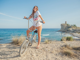 Young woman biking on seaside with dry grass on background of amazing turquoise seascape in bright day