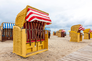 Strandkorb - colorful striped wooden hooded beach chairs. Sandy Baltic beach in Travemunde seaside resort near Luebeck city, Germany