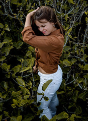 Cheerful beautiful woman standing in front of bushes touching back of head with hand looking away
