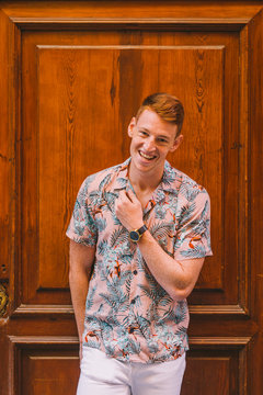 Handsome happy man male in hawaiian shirt leaning on wooden door looking at camera smiling