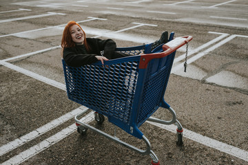Smiling woman sitting in shopping trolley in parking lot
