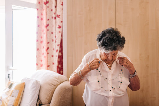 Elderly curly gray haired female in white shirt with hand on waist standing close armchair at nursing home