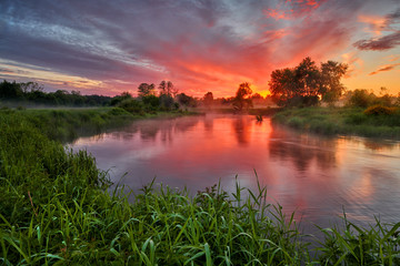 Beautiful summer sunrise over river banks Fototapete