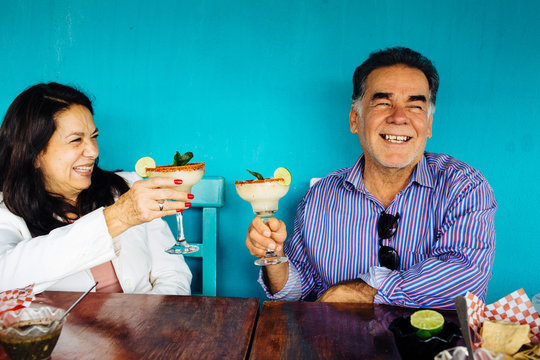 Hispanic Mexican woman and man senior couple celebrating cheering with margarita drink, Mexico