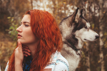 redhaired woman with her dog malamute outdoor in the autumn Wall mural