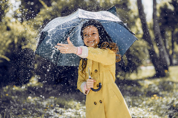 Little girl in a rain coat. Child playing in a park.