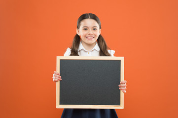 happy small school girl with chalkboard. blackboard for copy space. information. write hometask. back to school. happy teacher day. 1 september. small girl demonstrate announcement. school lunch menu