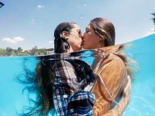 Two lesbian women having fun in swimming pool one summer afternoon Fototapete
