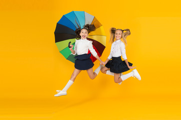 Fall weather forecast. Place for both of us. Fashion accessory. Girls friends with umbrella. Rainy day. Happy childhood. School time. Rainbow umbrella. Colorful life. Schoolgirls happy big umbrella