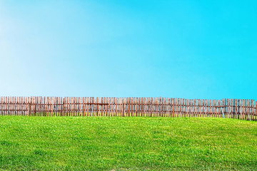 landscape of green lawn and blue sky divided in half by fence