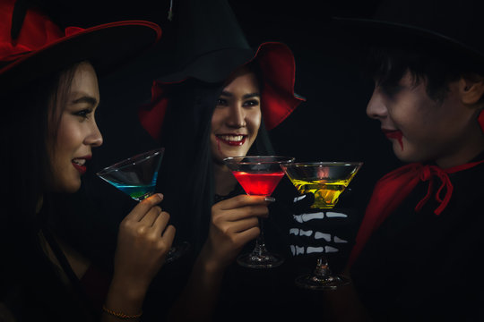 group of asian friends in spooky costume having fun and drink cocktails at halloween celebration party in nightclub