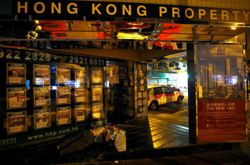 A man sleeps at the entrance of a real estate agent in Hong Kong