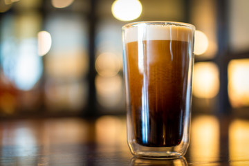 Beautiful texture and layers of Nitro Cold Coffee served in a dubble wall glass close up.