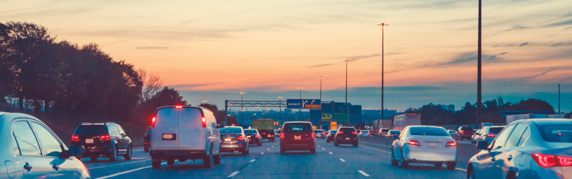 Night traffic. Cars on highway road at sunset evening in busy american city. Beautiful amazing urban view with red, yellow, blue sky. Sundown in downtown. Web header banner for website.