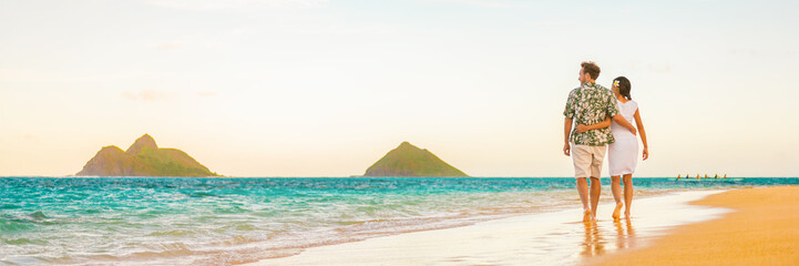 Couple walking on beach sunset vacation panoramic hawaii travel. Woman and man relaxing on tourist holiday in Lanikai, Oahu, Hawaii banner.