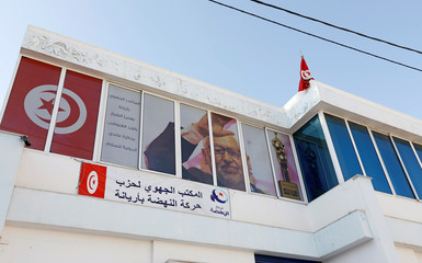 A picture of Rached Ghannouchi, leader of the moderate Islamist party Ennahda is seen on the windows of the party headquarters in Ariana