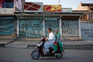 Kashmiris ride on a scooter past the closed shops painted with graffiti during restrictions, in Srinagar