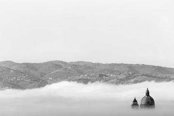 Surreal view of Santa Maria degli Angeli papal church (Assisi) almost completely hidden by fog