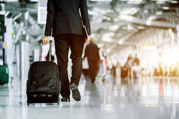 Elegant asian businessman checking email on mobile phone while walking with suitcase inside airport, experienced male employer using cell telephone while waiting for taxi car coming before work travel
