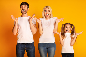 Amazed Parents And Daughter Screaming In Delight Over Yellow Background