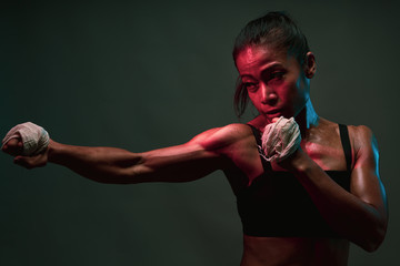 Close up of asian heathly woman shadow punching in boxing training with muscle fit lean tone body in pink and blue neon light on dark wall background, Concept martial art training. Wall mural