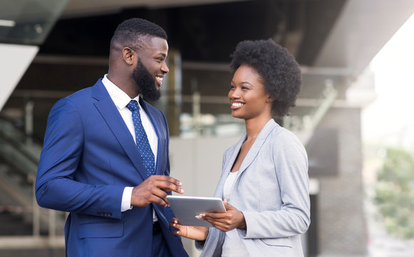 Handsome african coworker telling joke to his female partner