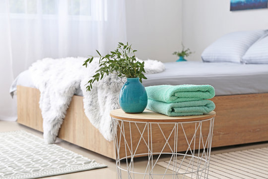 Stack of clean towels on table in bedroom