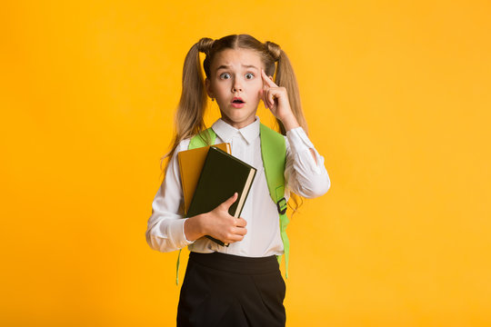 Embarassed Elementary Student Looking At Camera Holding Books On Yellow Background