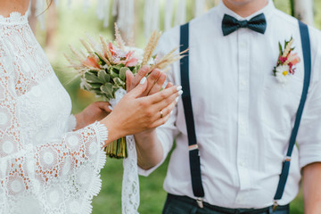 Crop photo of bride young woman with the boho style bouquet with groom on wedding ceremony in forest