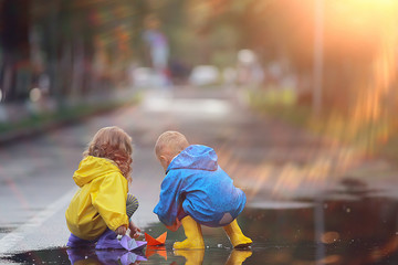 brother and sister play boats in a puddle / raincoats clothes, autumn weather children play paper boats
