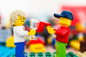 Two Lego man character figures holding glass and cup and looking at each other while having a talk on February 15, 2019 in Poznan, Poland.