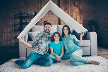 Portrait of cheerful family with brunette hair holding wearing checkered plaid shirt denim jeans t-shirt sitting on floor indoors