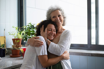 Fototapeta Smiling mother and daughter hugging. Happy senior mother and adult brunette daughter with closed eyes hugging at home. Family concept obraz