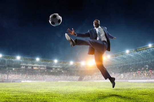 Black businessman in a suit playing footbal