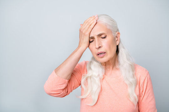 Reaction on magnetic storm hot warm weather and global warming concept. Close up photo of sad upset nervous in bad condition old lady having acute periodical pain isolated grey background
