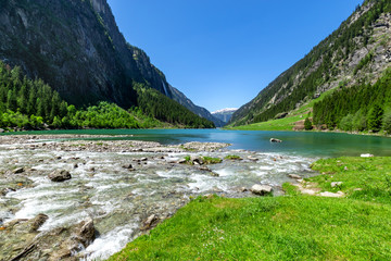 Fast water stream flow into mountain lake. Summer mountain landscape in the Alps, Austria, Tyrol.