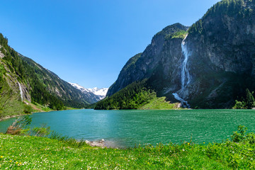 Wall Mural - Mountain landscape with clear turquoise lake and waterfall in the Alps. Zillertal Alps Nature Park, Austria, Tyrol.