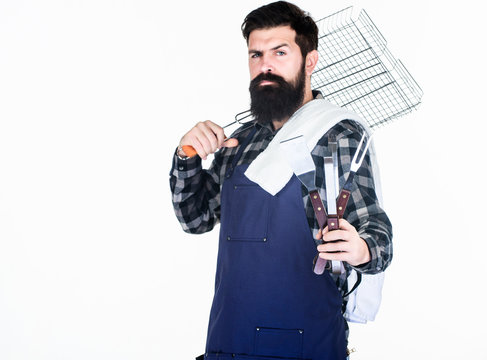 Tools for roasting meat outdoors. Picnic and barbecue. Cooking meat in park. Masculine hobby. Bearded hipster wear apron for barbecue. Roasting and grilling food. Man hold cooking utensils barbecue